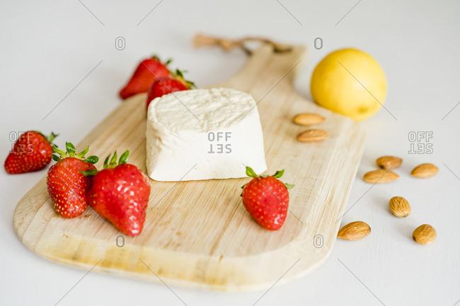Wooden cutting board- fresh strawberries- almonds and homemade vegan cheesecake