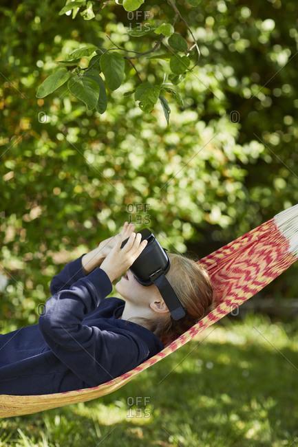 Girl in hammock wearing VR glasses