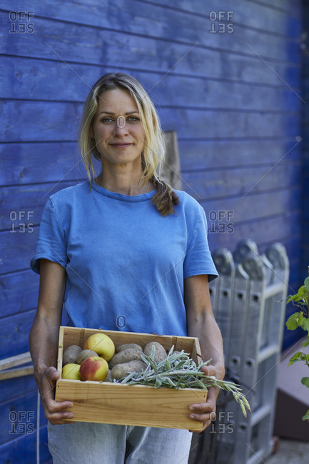 Portrait of woman holding a crate at garden shed