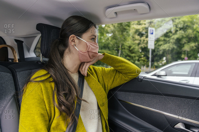 Young woman wearing protective mask sitting on back seat of car looking out of car window