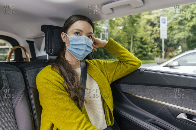 Portrait of pensive young woman wearing protective mask sitting on back seat