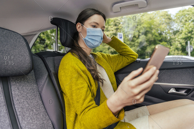 Young woman wearing protective mask sitting on back seat of car looking at cell phone