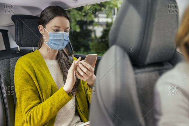 Young woman wearing protective mask sitting on back seat of car using cell phone