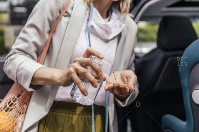Car driver disinfecting hands after shopping- close-up