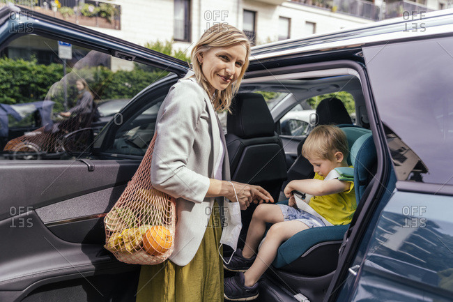 Portrait of smiling woman waiting in front of car while her little son fastening seat bell of child's seat