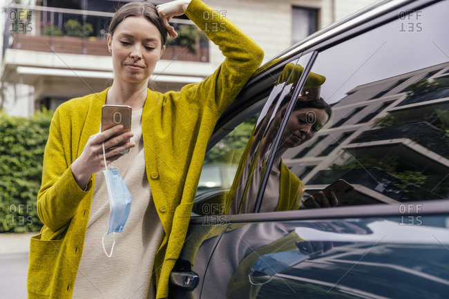 Portrait of young woman with protective mask leaning on her car while looking at cell phone