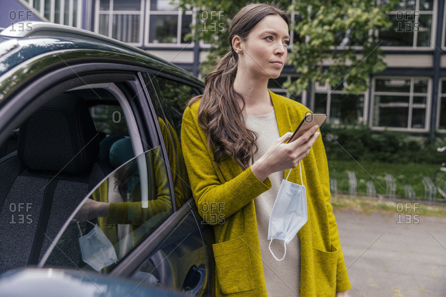 Portrait of young woman with cell phone and protective mask leaning at car looking at distance