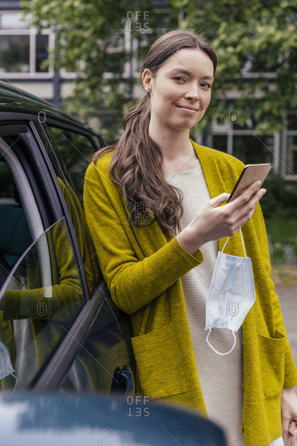 Portrait of smiling young woman with protective mask and cell phone leaning at car