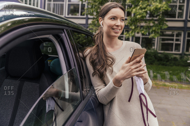 Portrait of smiling young woman leaning against car listening music with earphones and cell phone