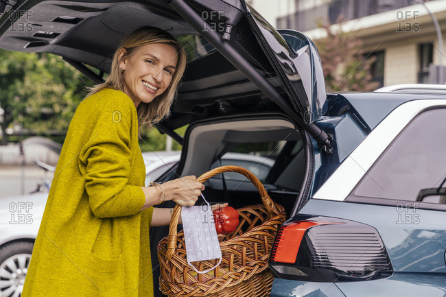 Portrait of happy woman with protective mask putting purchase in trunk of her car