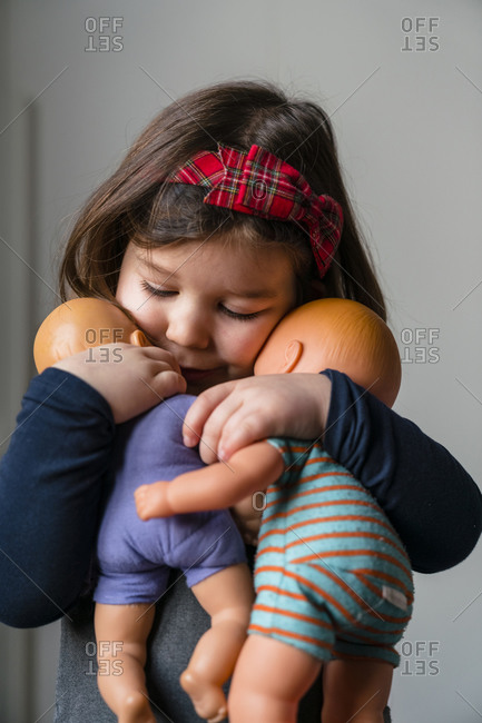 Close-up of cute girl embracing her dolls at home