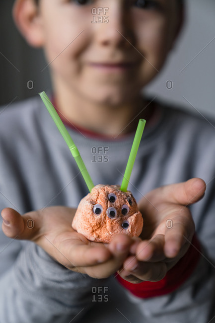 Close-up of boy holding toy alien made from clay and straw at home