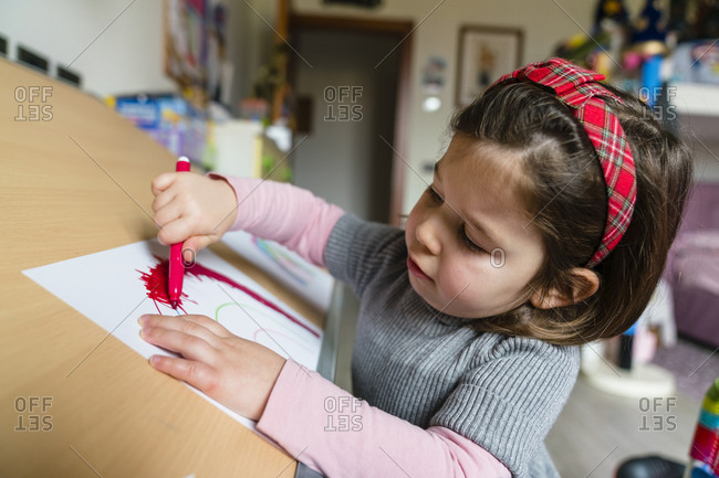 Cute preschool girl drawing on paper at home