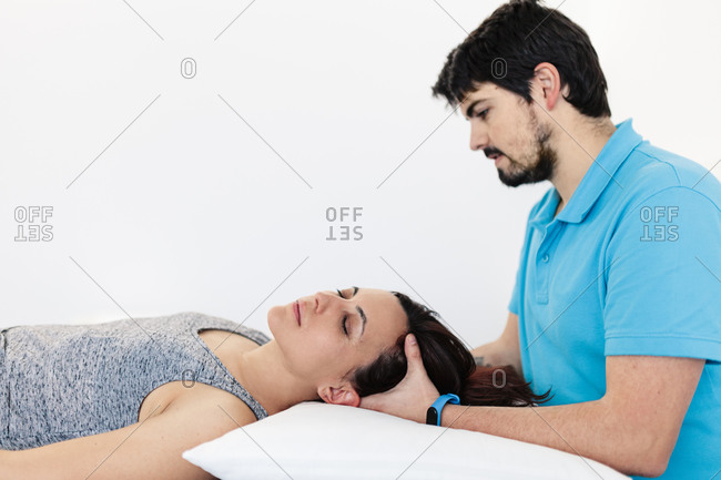 Visually impaired physical therapist massaging woman's head in clinic