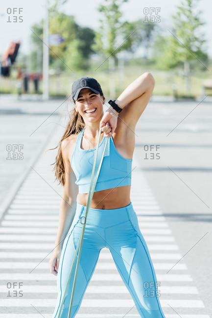 Portrait of happy young woman exercising with resistance band on sunny day