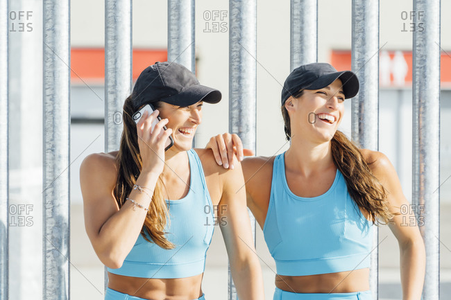Smiling young woman talking on mobile phone by twin sister against fence