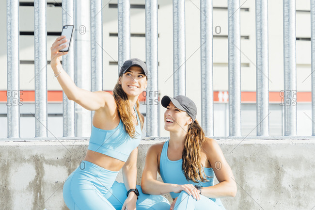 Young woman taking selfie with twin sister against fence from smart phone