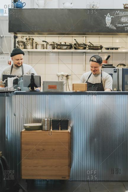 Male chefs preparing food behind kitchen counter in restaurant