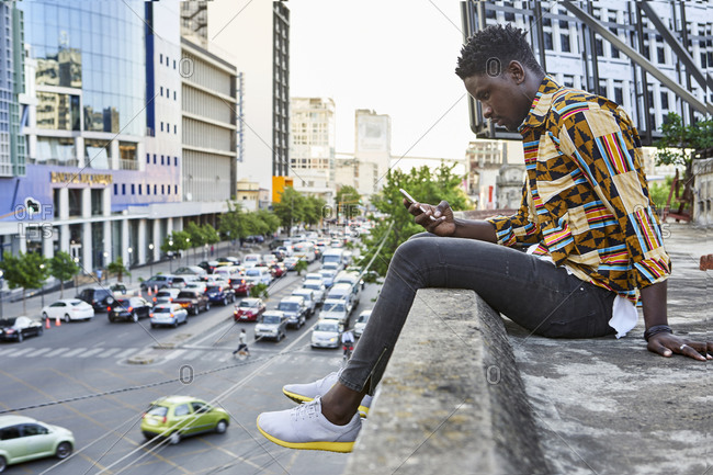 Young man in patterned shirt sitting on roof terrace in the city checking his phone- Maputo- Mozambique