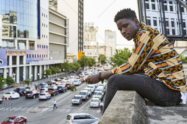 Young man in patterned shirt sitting on roof terrace in the city- Maputo- Mozambique