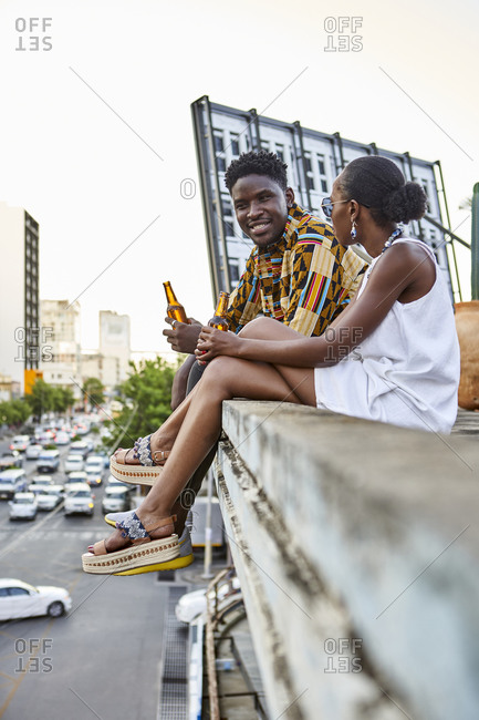 Couple sitting on roof terrace in the city drinking beer- Maputo- Mozambique