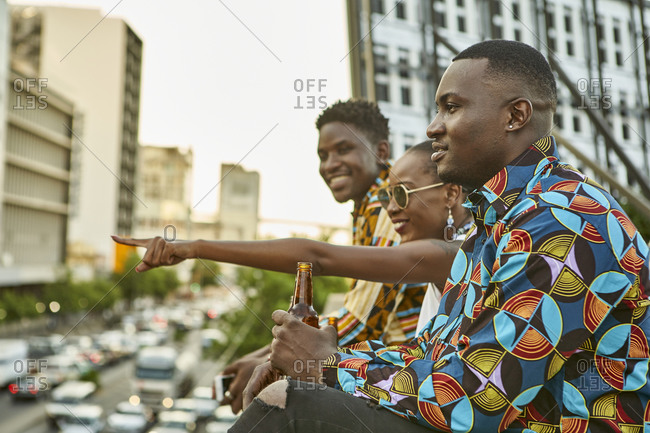 Friends sitting on roof terrace in the city drinking beer- Maputo- Mozambique
