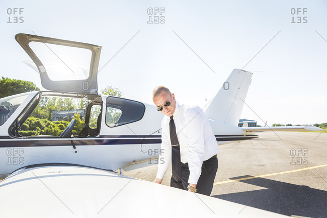 Pilot doing pre flight inspection on his sports plane