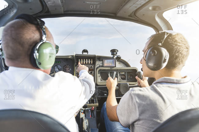 Pilot and copilot navigating sports plane- rear view