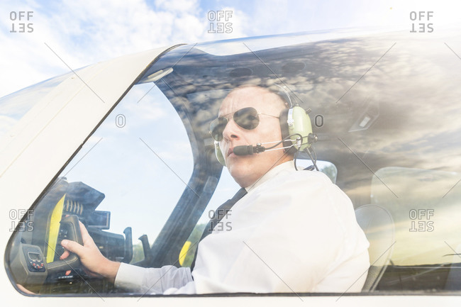 Pilot with headset- sitting in sports plane