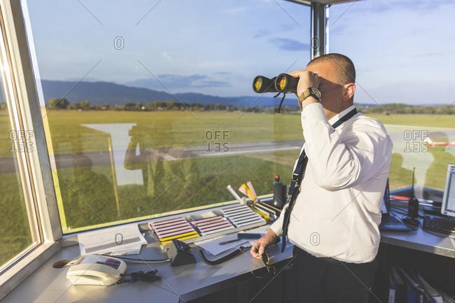 Pilot standing in control tower- using binoculars