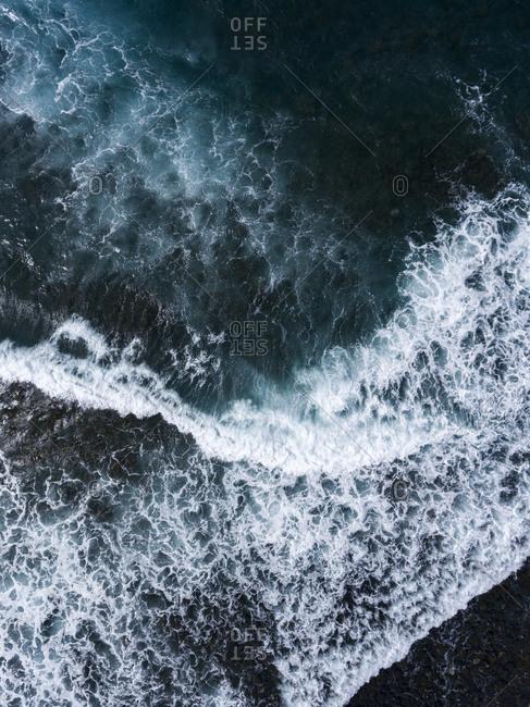 Bird's eye view of foamy ocean waves during a storm