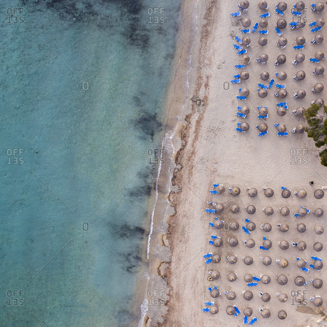 Empty beach with umbrellas and blue lounge chairs by the sea