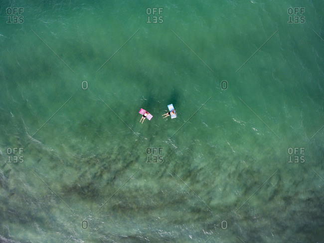 Aerial view of two women drifting in the sea