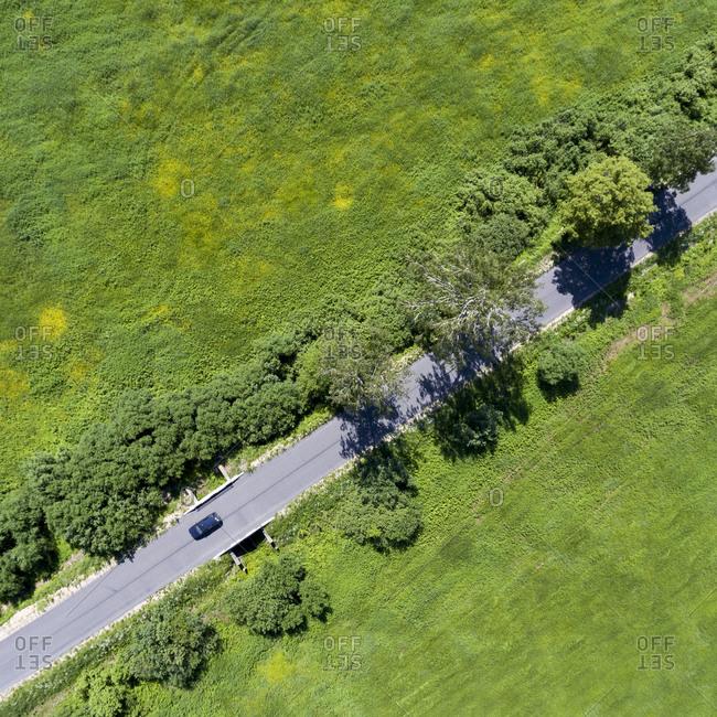 Car driving across green landscape