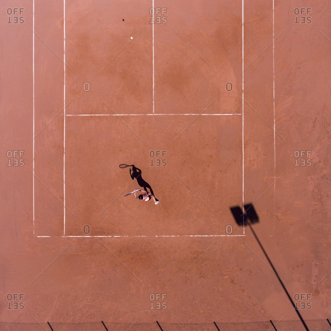 Bird's eye view of tennis player on a red court