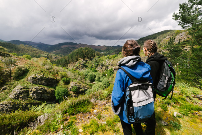 Back view of unrecognizable female hikers in outerwear standing on rocky hill and admiring amazing view of highland scenery during sunny day