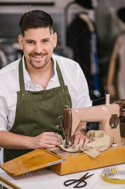 Diligent focused male tailor in apron sewing outfit details using modern sewing machine at table while creating exclusive clothes collection in contemporary work studio