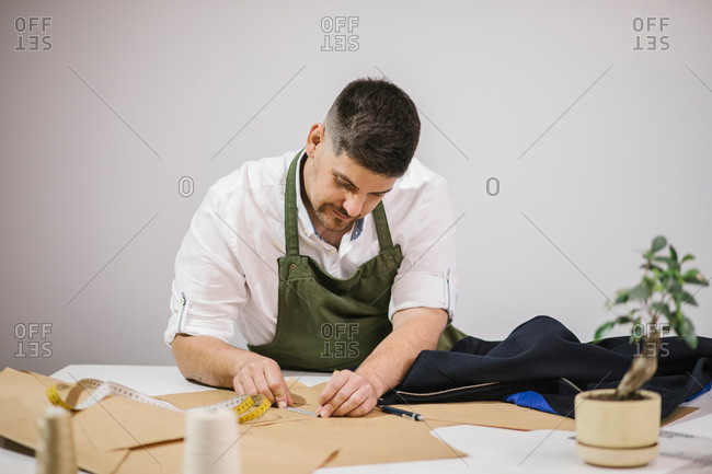 Male seamstress using measuring tape while checking exact size of patterns while making bespoke outfit for client in modern atelier