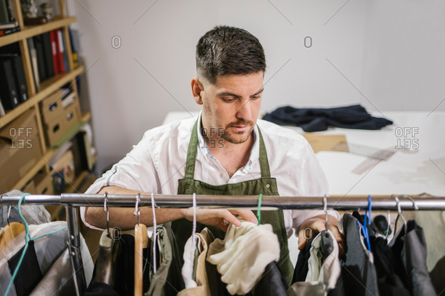 High angle of serious focused male tailor in apron checking details of apparel hanging on hanger on metal rack among other trendy bespoke clothes in modern workroom