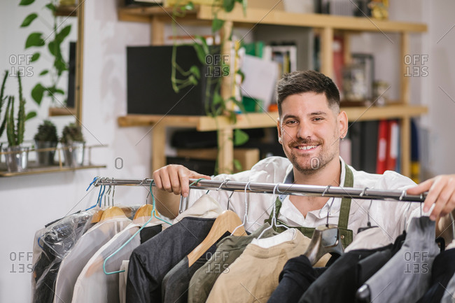 High angle of happy focused male tailor in apron checking details of apparel hanging on hanger on metal rack among other trendy bespoke clothes in modern workroom
