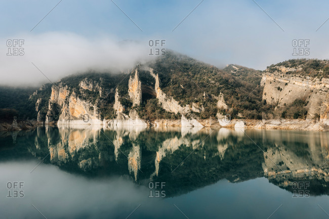 Magnificent landscape of calm lake with mirrored water surface surrounded by rough rocky mountains of Montsec Range covered with dense fog in cold day in Spain