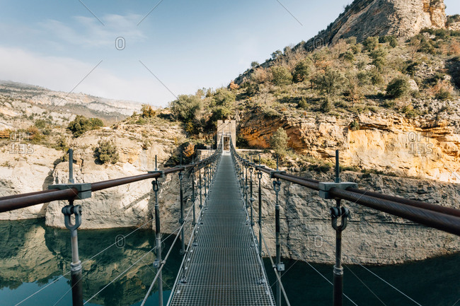 Empty narrow pedestrian bridge suspended over river and connecting rough rocks of Montsec range in Spain