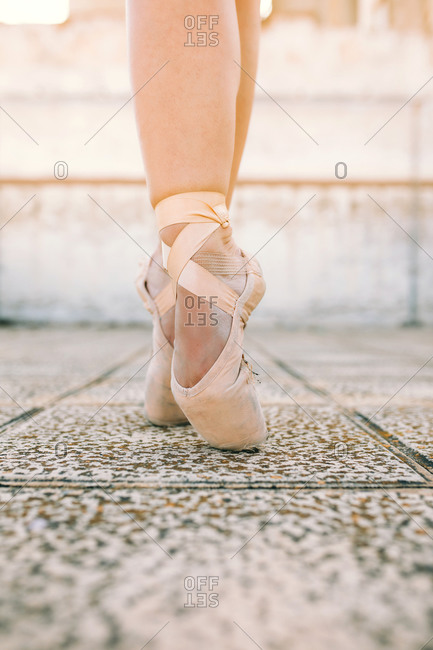 Crop female dancer wearing pointe shoes standing on tiptoes on weathered stone ground and demonstrating dancing position