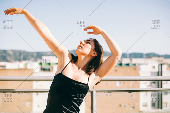 Graceful female dancer in moment of performing element with outstretches arms looking up on summer terrace on background of palm trees