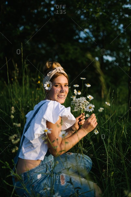Side view of young woman looking at camera in casual clothes enjoying smell of fresh chamomiles while collecting flowers on green meadow in spring