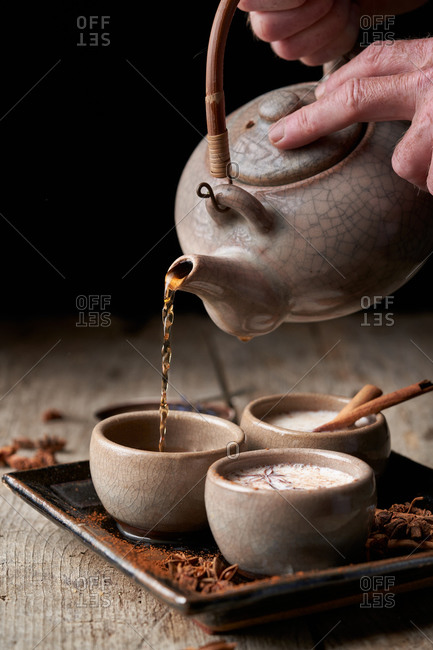 Crop person with teapot pouring Masala chai in ceramic bowls placed on tray with star anise and cinnamon sticks