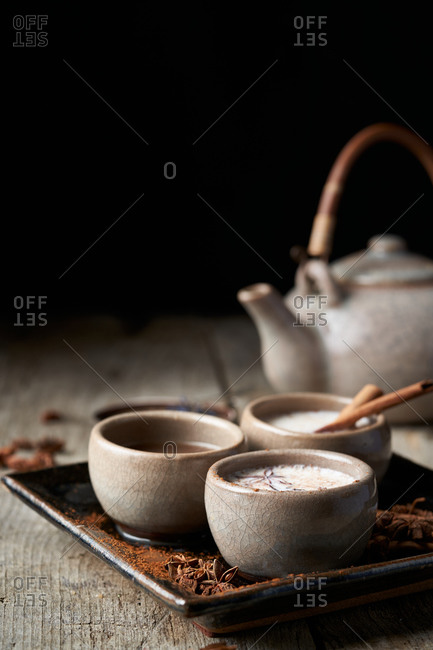 Masala chai served in ceramic bowls with star anise and cinnamon sticks arranged on wooden table with teapot and piece of cloth