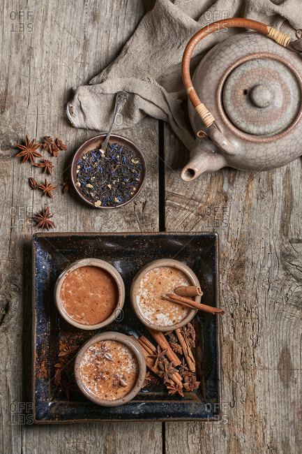 Top view of Masala chai served in ceramic bowls with star anise and cinnamon sticks arranged on wooden table with teapot and piece of cloth