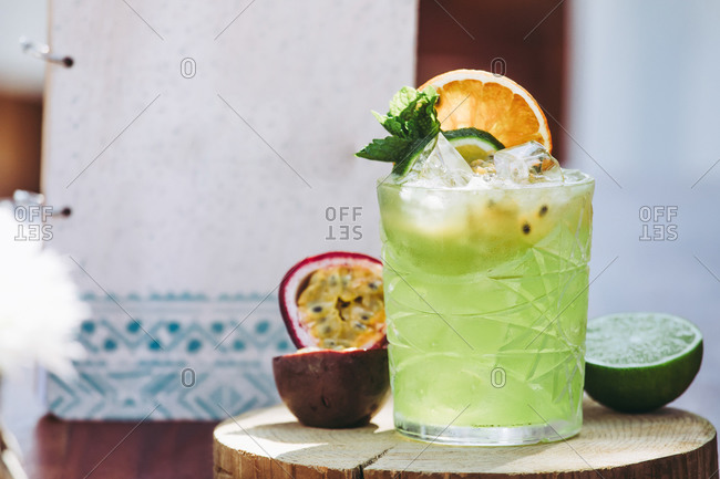 Glass of cold green alcohol Mojito cocktail with fresh passion fruit and lime garnished with mint leaves and fruit slices