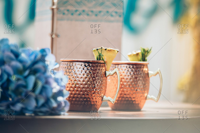 Cold Moscow Mule cocktail with ginger beer and vodka with lime served in traditional copper mugs on bar counter with flowers